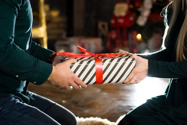 Ręce z prezentami na boże narodzenie i nowy rok, czerwona zieleń, ciążowa niespodzianka