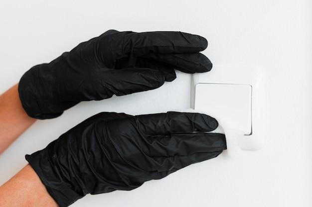 Ręce z rękawiczkami chirurgicznymi do dezynfekcji włącznika światła