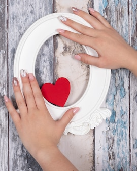 Ręce z żelowymi paznokciami trzyma czerwone serce i białą ramkę