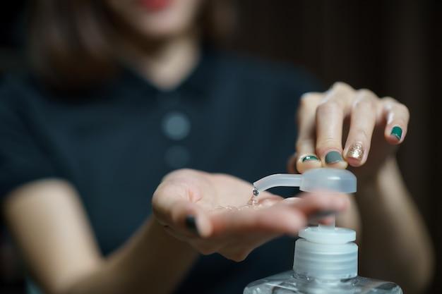Ręce za pomocą dozownika żelowej pompy do dezynfekcji rąk. przezroczysty środek dezynfekujący w butelce z pompką do zabijania zarazków, bakterii i wirusów.