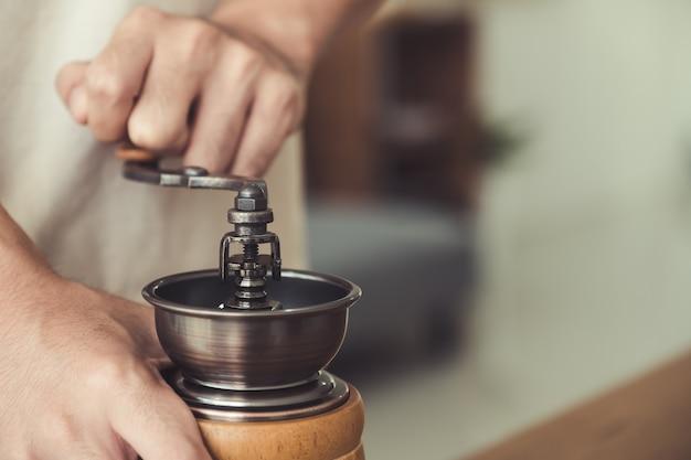 Ręce za pomocą młynka do mielenia ziaren kawy