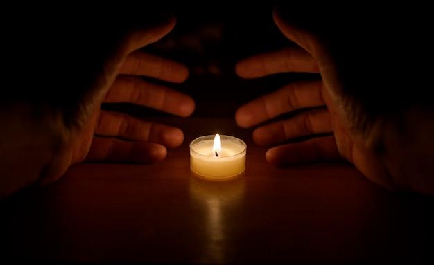 Ręce zakryły świecę