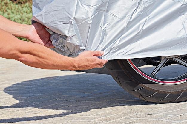 Ręce zakrywają tylne koło motocykla wodoodpornym pokrowcem ochronnym