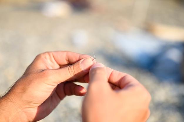 Ręce zawiązujące żyłkę na haczyku