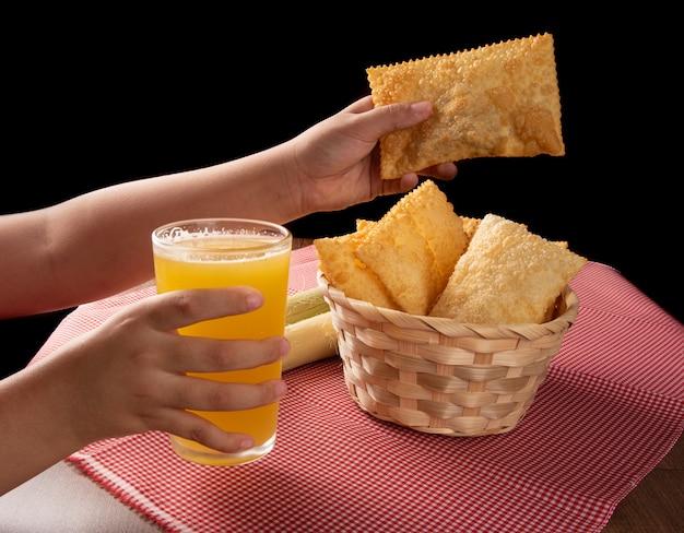 Ręce zbierające brazylijskie smażone pasta i szklankę soku z trzciny cukrowej