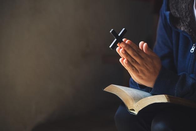 Ręce złożone do modlitwy na świętą biblię w kościelnym pojęciu wiary