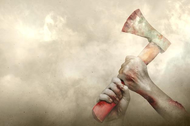 Ręce zombie z raną trzymającą siekierę z mglistym tłem