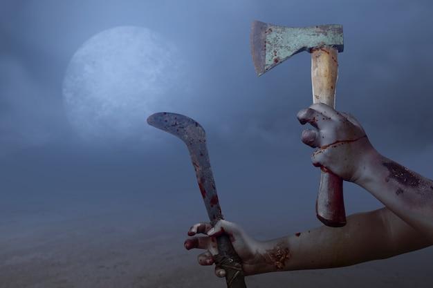 Ręce zombie z raną trzymającą sierp i siekierę na tle nocnej sceny