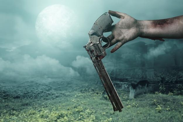 Ręce zombie z raną upuszczają pistolet na tle nocnej sceny
