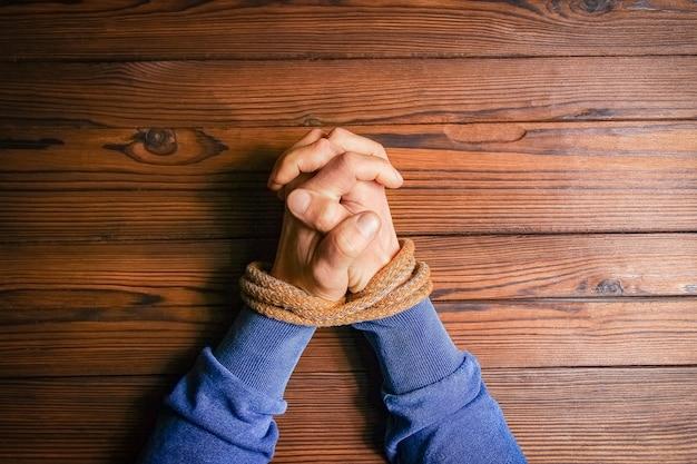Ręce związane liną zagrażającą życiu na drewnianym tle.