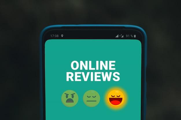 Recenzje online usługi lub organizacja. ekran telefonu komórkowego z uśmiechami emotikonów