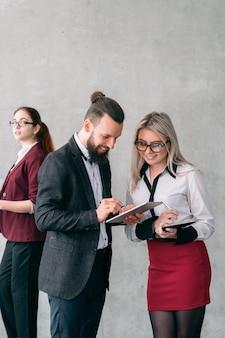 Recenzje opinii biznesowych. bliscy koledzy. uśmiechnięci członkowie zespołu przeglądający tablet.