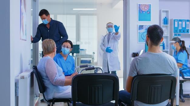 Recepcja prywatnego szpitala podczas globalnej pandemii. lekarz z wizjerem przeciwko koronawirusowi zapraszający mężczyznę do swojego gabinetu na badanie. niepełnosprawna starsza kobieta z balkonikiem