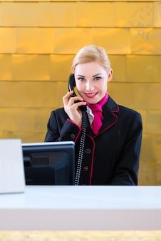 Recepcjonista hotelu z telefonem na recepcji