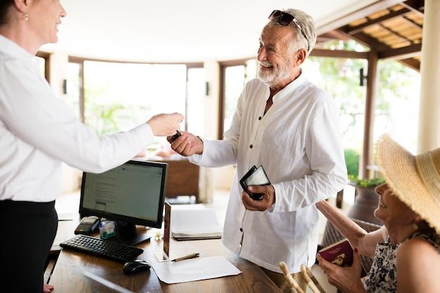 Recepcjonista recepcyjny podający klucz do pokoju dla gościa