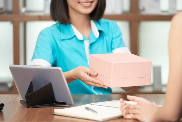 Recepcjonista upraw, dając klientowi pudełko upiększające