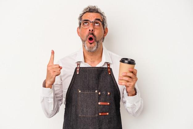 Recepcjonista w średnim wieku trzyma kawę na wynos na białym tle, wskazując do góry nogami z otwartymi ustami.