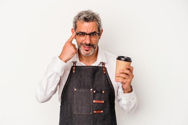 Recepcjonista w średnim wieku trzymający kawę na wynos na białym tle pokazujący gest rozczarowania palcem wskazującym.