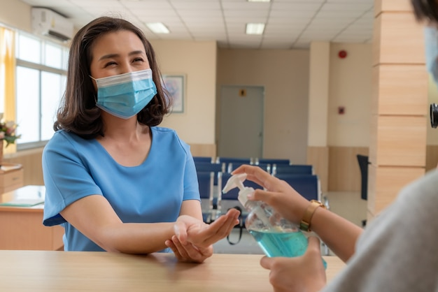 Recepcjonistka i gość noszący maskę w recepcji.