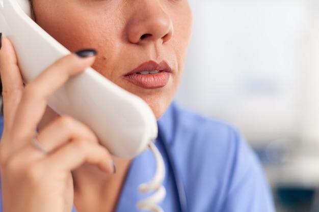 Recepcjonistka medyczna odbiera telefony od pacjenta w szpitalu