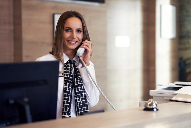 Recepcjonistka odbierająca telefon w recepcji hotelu