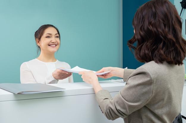 Recepcjonistka przyjmuje dokumenty od kobiety odwiedzającej.