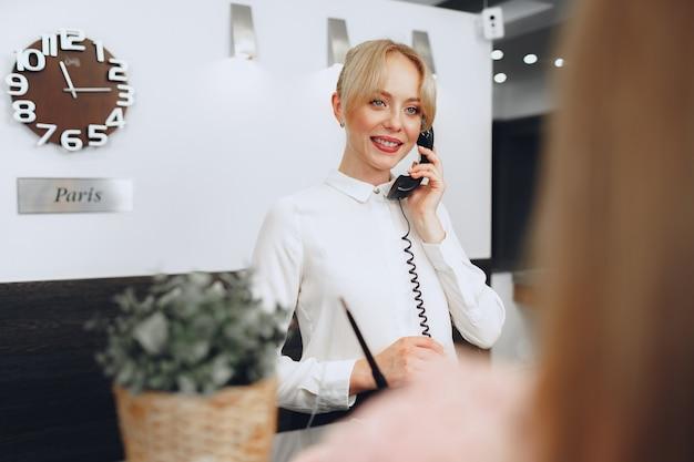 Recepcjonistka w hotelu rozmawia przez telefon w pracy