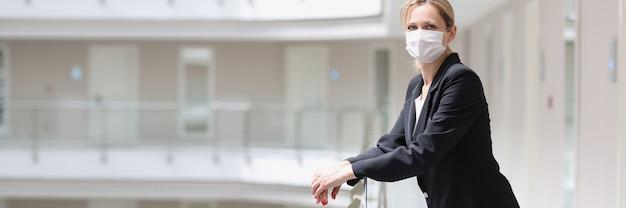 Recepcjonistka w medycznej masce ochronnej stoi na korytarzu kompleksu hotelowego