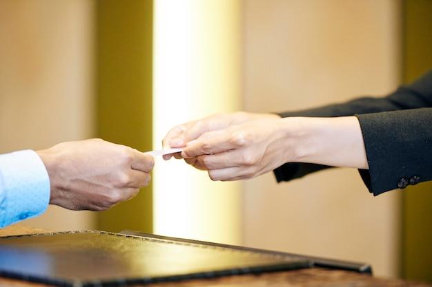 Recepcjonistka wręcza klucz gościowi