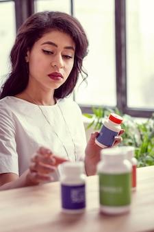 Recepta lekarzy. inteligentna, dobrze wyglądająca kobieta, patrząc na swoje lekarstwo, wybierając, który z nich wziąć
