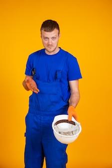 Recesja w gospodarce. pracownik wyciąga pusty biały kask ochronny. mężczyzna w kombinezonie bez pracy. recesja i kryzys gospodarczy, bezrobocie
