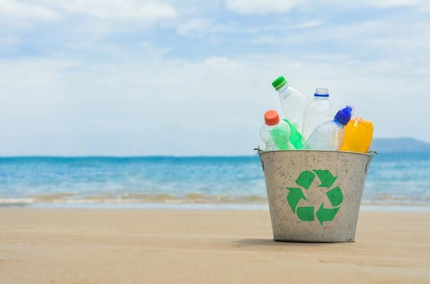 Recykling, kosz z plastikową butelką na plaży