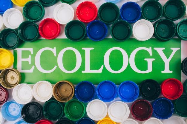 Recykling, ponowne użycie, ograniczenie koncepcji. słowo ekologia w centrum kolorowego tła różne plastikowe pokrywki, widok z góry. recykling pokryw butelek. jednorazowe tworzywa sztuczne, dyrektywa europejska ue. oszczędzaj ekologię