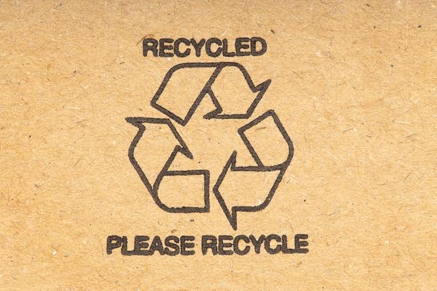 Recykling symbol na brązowym tle kartonu z recyklingu. ścieśniać