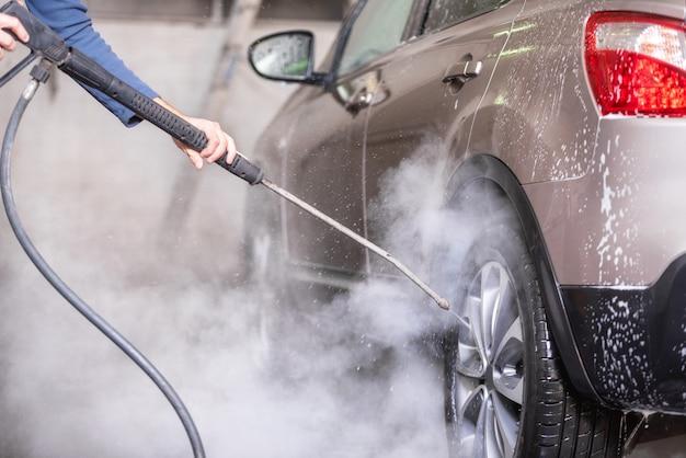 Ręczna myjnia samochodowa z wodą pod ciśnieniem w myjni samochodowej na zewnątrz.