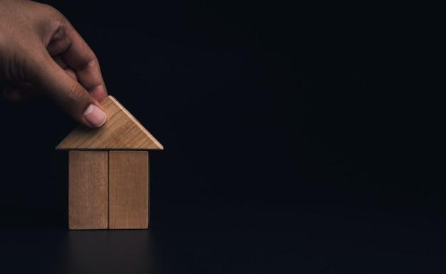 Ręczne budowanie domu z drewnianych klocków, układanie dachu na ciemnym tle z miejsca kopiowania. planowanie nieruchomości. symbol budowy domu, styl eko, koncepcje kredytowe.