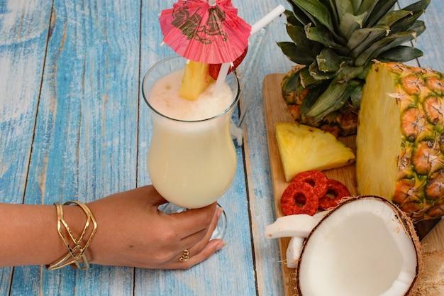 Ręczne chwytanie piña colady ze świeżymi owocami na drewnianej desce do krojenia na tle stołu białej tablicy
