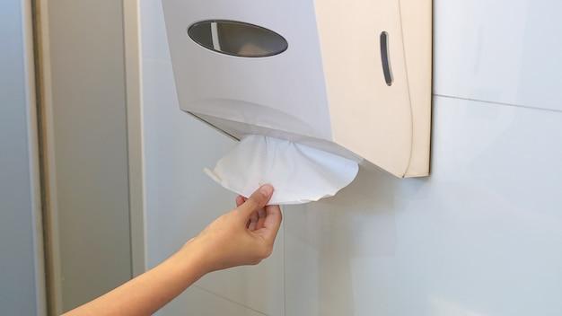 Ręczne ciągnięcie papieru toaletowego w łazience