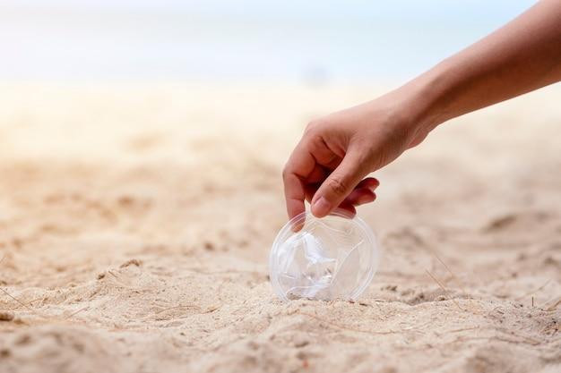 Ręczne czyszczenie i zbieranie plastikowych szklanych śmieci na plaży