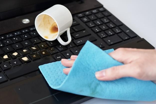 Ręczne czyszczenie szmatką rozlanej kawy na klawiaturze laptopa