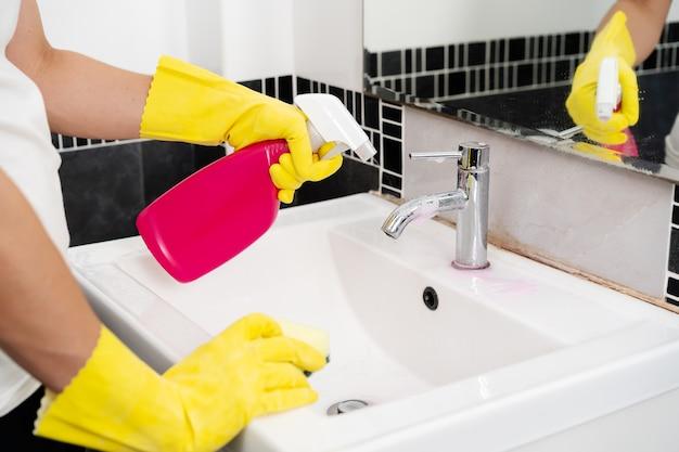 Ręczne czyszczenie umywalki łazienkowej za pomocą detergentu w sprayu i gąbki