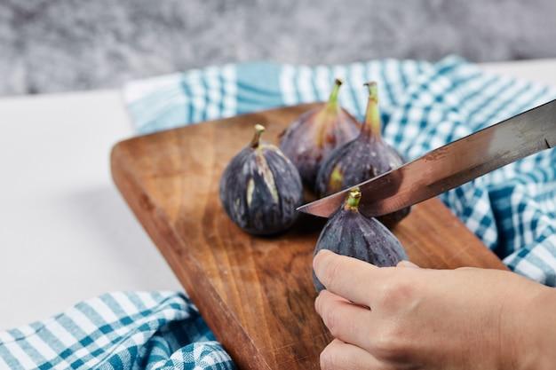 Ręczne krojenie fig na drewnianej desce do krojenia z niebieskim obrusem.