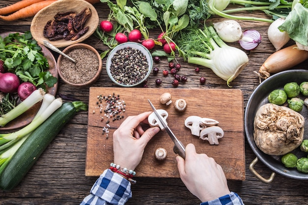 Ręczne krojenie warzyw. ręce kobiet kroi grzyby na desce w pobliżu warzyw.