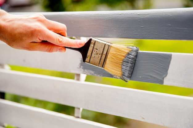 Ręczne malowanie białych desek drewnianych szarą farbą za pomocą pędzla.