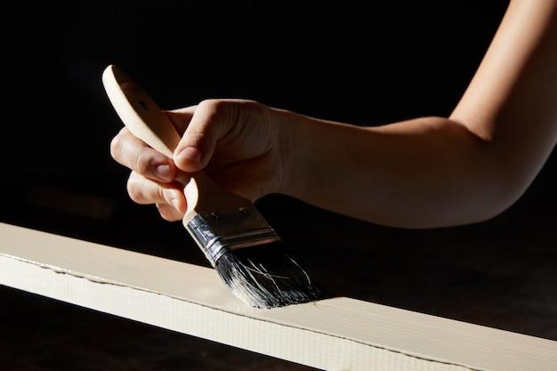 Ręczne malowanie powierzchni deski z naturalnego drewna na biały kolor;