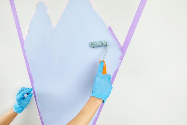 Ręczne malowanie ścian wałkiem do malowania i malowanie taśmą maskującą remont mieszkania w kolorze niebieskim with