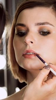 Ręczne nakładanie szminki na klienta