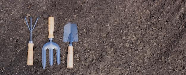 Ręczne narzędzia ogrodowe na czarnej żyznej glebie