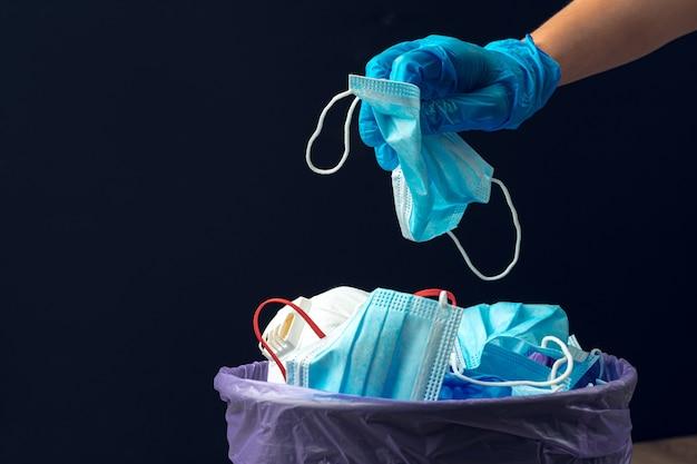 Ręczne oddawanie używanej brudnej maski chirurgicznej do kosza na śmieci z bliska
