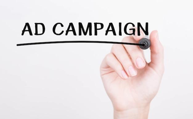 Ręczne pisanie kampanii reklamowej z czarnym markerem na przezroczystej tablicy do wycierania